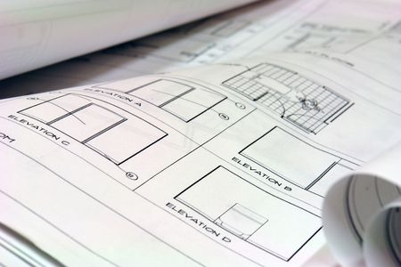 close up of blue prints laid out on desk photo