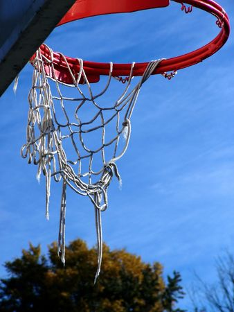 orange basketball hoop with white tattered strings set off against a rich blue sky, trees in the background, easthampton, massachusetts 版權商用圖片