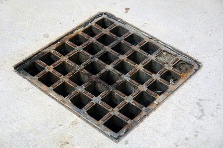 angled view: Angled view of aged storm drain  surrounded by cement