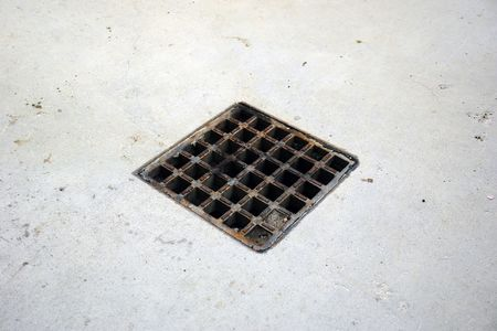 Angled view of aged storm drain  surrounded by cement
