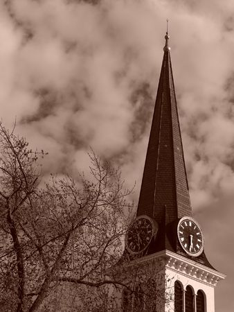 pilaster: Sepia toned image showing steeple of old new england church in the spring time with tree in bloom and thick clouds