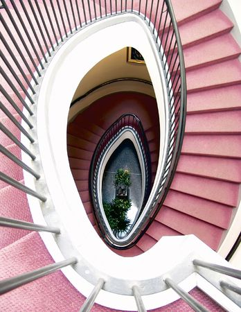 shot from above, looking down the center of a spiral stair case covered in red carpet, statue and green plant  is on the tile floor below, public library, newton, massachusetts, new england Stock Photo - 708763