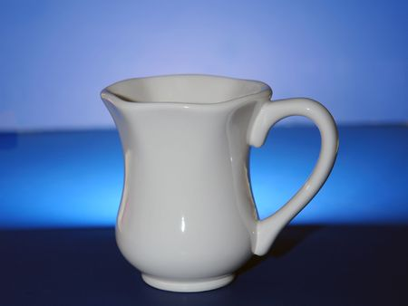 white fluted coffee cup with handle  on multi shaded blue background Banco de Imagens