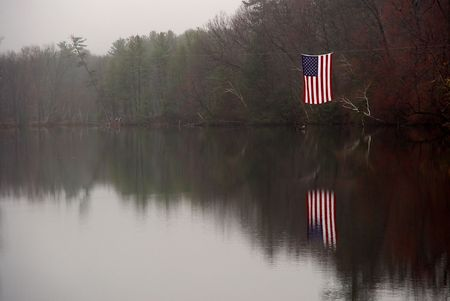 the american flag hangs suspended over the nashawannuck pond in easthampton massachusetts, the pond is still with misty fog Banco de Imagens