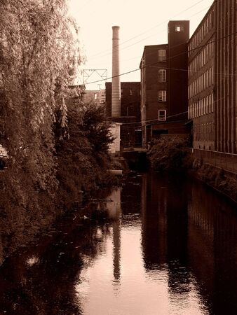 smoke stack: sepia image of canal behind old factory building in easthampton massachusetts, on the left is a bank of trees, on the right a bank of factory windows, in the center a smoke stack