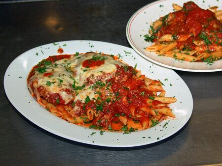freshly prepared: two freshly prepared meals in the kitchen of an italian restaurant, ziti, chicken parmesan on white china