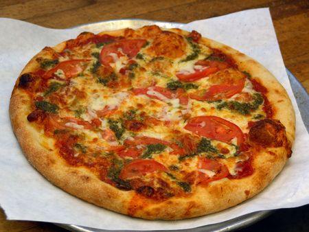 unsliced: freshly baked pizza pie in kitchen of italian restaurant, unsliced