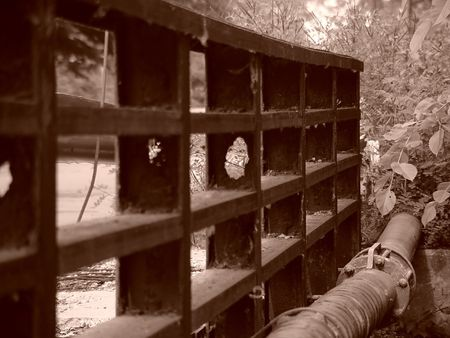 sewer pipe: sepia image of old walking bridge in easthampton massachusetts, the metal rail has rotted and the sewer pipe is collapsing, there is a lot of over growth