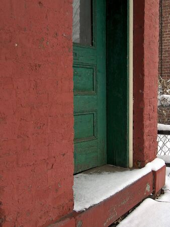 stoop: Green door in red wall with snow on the stoop