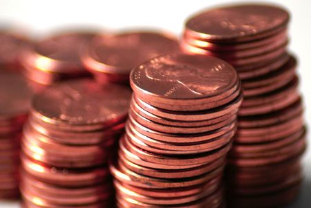 penny pinching: close up of stacks of pennies against a white background