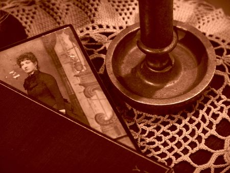 Sepia toned image of old fashioned still life with candlestick, photo, lace doily, and photo       版權商用圖片