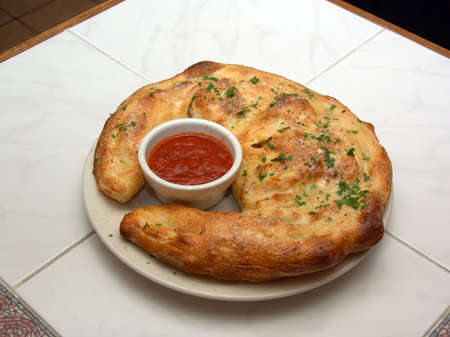 Fresh baked golden brown calzone on dinner plate on marble counter wrapped around a small bowl of marinara sauce Stock Photo