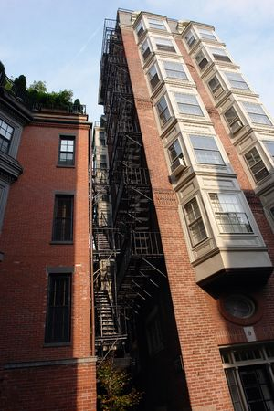 image of an old tall apartment building in downtown boston showing two rows of bay windows and full fire escape photo