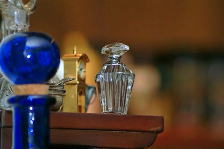 Crystal perfume bottle sitting on shelf with miniature gradfather clock, with blue bottle in foreground