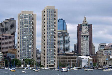 encrespado: Vista de la ciudad de boston boston puerto mostrando diversos rascacielos de diferentes �pocas. El mar est� picado y el cielo nublado  Foto de archivo
