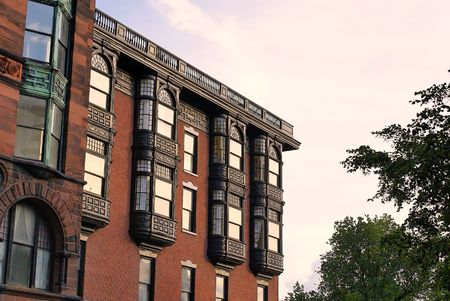 brownstone: Upper floors of old brownstone apartment building in boston, massachusetts on a spring afternoon. showing ornate glass work, iron work and brick work