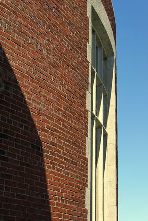 Curved brick wall with cement window panes against a blue sky