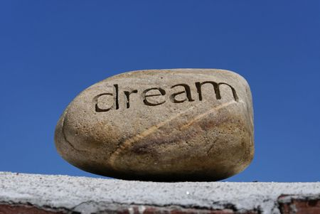dreams put on the shelf, a rock with the word dream inscribed in it  sits on top of a brick wall against a deep blue sky Stock Photo