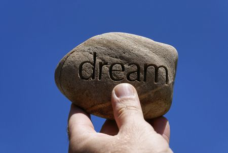 inscribed: man holding his dreams in his hands. holding firm to solid dreams. holding your dreams high, a rock with the word dream inscribed in it