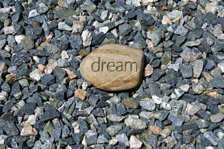 inscribed: a big dream rock stands out among smaller stones, a rock with the word dream inscribed in it  Stock Photo