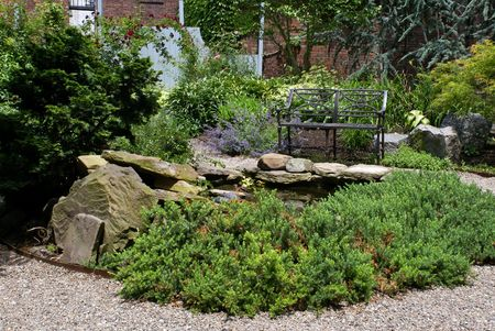 A rock pond and bench located in lush colorful private urban garden