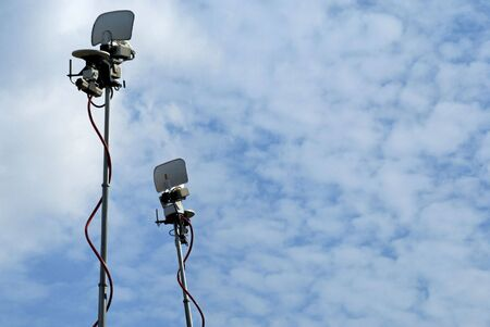 newscast: Television satellite camera antennas high up in the sky providing live feed for news casts
