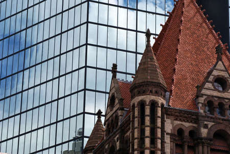 vividly: the sky is vividly reflected on large glass mirrored skyscraper building in bostons back bay behind trinity church in copley square