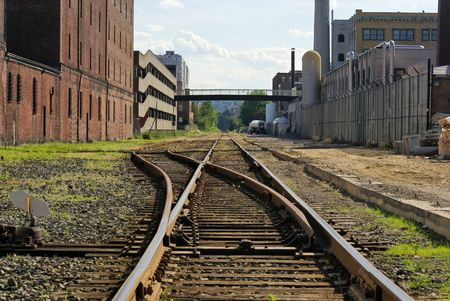 switching: railroad track switching station converging in the distance in cambridge massachusetts flanked by factory buildings