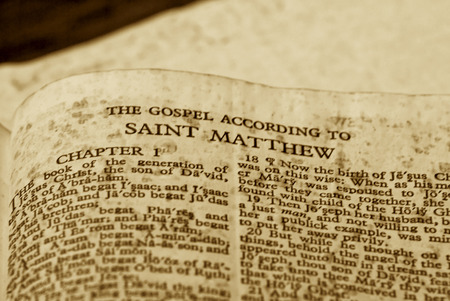 Old looking sepia toned close up of page from bible, the gospel according to saint matthew Stock Photo