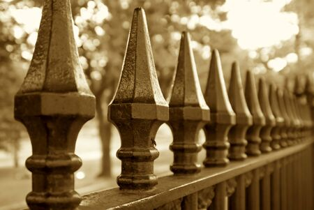 trailing: sepia toned image of wrought iron fence trailing off into the distance Stock Photo