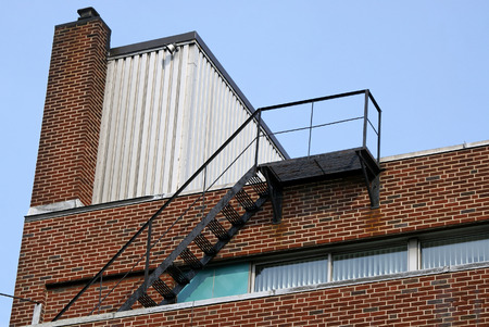 Top of brick building showing chimney, fire escape and row of small windows against a pale blue sky