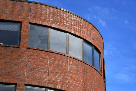 majestic yet simple curved brick building  against a light blue sky with soft clouds located in harvard square, cambridge massachusetts 스톡 콘텐츠