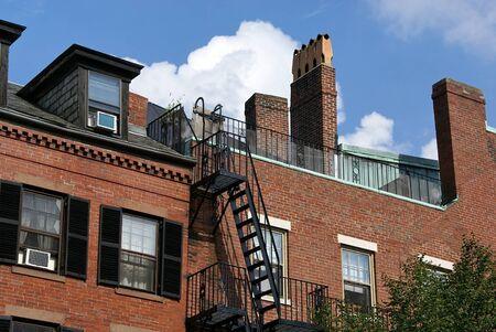 rij huizen: rij huizen blijkt dak dek en brandtrap langs Charles Street in Boston met cumulous wolken op de achtergrond