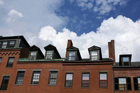 row houses: case a schiera lungo la strada di charles in boston con nuvole cumulous in background Archivio Fotografico