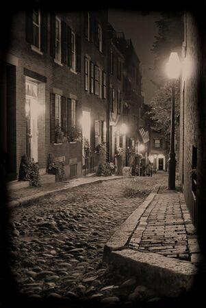 cobble: Seppia tonica immagine del 19 � secolo una vecchia strada in pietra, affastellate Boston Massachusetts, illuminato solo da lampade a gas rivelando il shuttered illuminate le finestre e le porte della rowhouses su Acorn Street