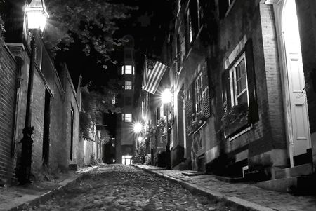 19th century: black and white night image of an old 19th Century cobble stone road in Boston Massachusetts, lit only by the gas lamps revealing the shuttered windows and brightly lit doorways of the rowhouses on Acorn Street
