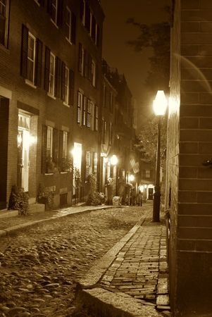 19th century: Sepia toned image of an old 19th Century cobble stone road in Boston Massachusetts, lit only by the gas lamps revealing the shuttered windows and brightly lit doorways of the rowhouses on Acorn Street