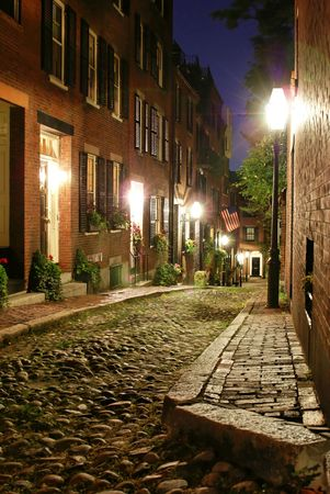 19th century: night time image of an old 19th Century cobble stone road in Boston Massachusetts, lit only by the gas lamps revealing the shuttered windows and brightly lit doorways of the rowhouses on Acorn Street Stock Photo