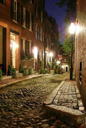 cobble: notte tempo immagine di un vecchio 19 � secolo Cobble pietra strada a Boston Massachusetts, illuminato solo da lampade a gas che rivelano l'shuttered finestre e porte illuminate del rowhouses a Acorn Street