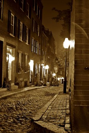 rowhouses: sepia image of an old 19th Century cobble stone road in Boston Massachusetts, lit only by the gas lamps revealing the shuttered windows and brightly lit doorways of the rowhouses on Acorn Street