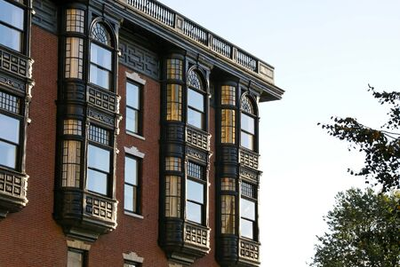brownstone: Upper floors of old brownstone apartment building in boston, massachusetts on a fall afternoon. showing ornate glass work, iron work and brick work Stock Photo
