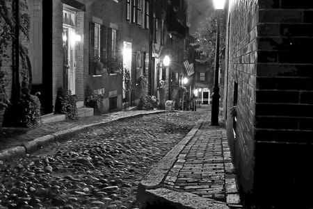 rowhouses: black and white image of an old 19th Century cobble stone road in Boston Massachusetts, lit only by the gas lamps revealing the shuttered windows and brightly lit doorways of the rowhouses on Acorn Street