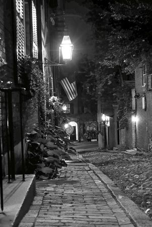 19th century: black and white night image of an old 19th Century cobble stone road in Boston Massachusetts, lit only by the gas lamps revealing the shuttered windows and brightly lit doorways of the rowhouses on Acorn Street, you can almost feel the night coming down