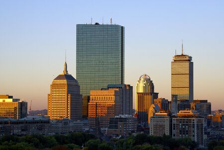 the warm color of the sun bathes the boston skyline on a cool autumn morning photo