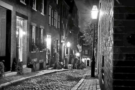 rowhouses: old 19th Century cobble stone road in Boston Massachusetts, lit only by the gas lamps revealing the shuttered windows and brightly lit doorways of the rowhouses on Acorn Street