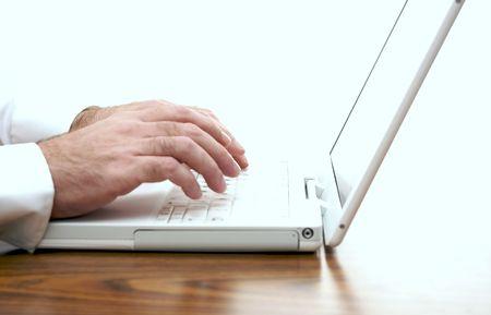 흰색 노트북의 키보드에 입력하는 책상에 앉아 남자