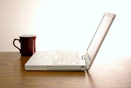 赤のコーヒー カップが机の上に座って近代的な白い norebook ラップトップ コンピューター 写真素材