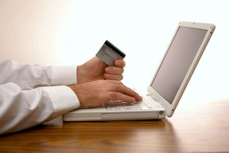 man sitting at desk placing order with credit card on laptop Stock Photo