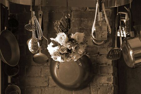 sepia toned image of country kitchen with roses hanging from the pot rack drying
