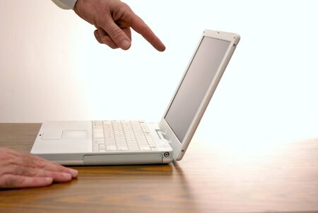 lap top: man pointing at laptop computer screen another hand is resting on desk